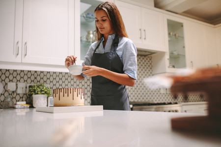 Woman preparing chocolate cake at home