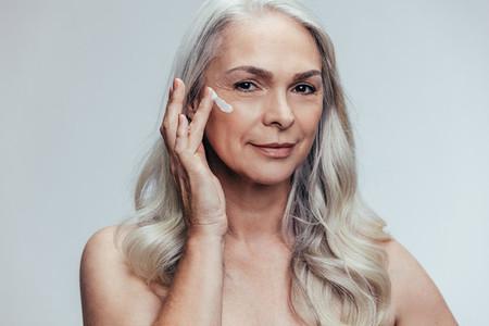 Senior woman applying anti aging face cream