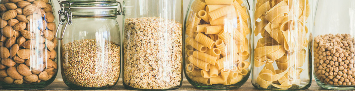Uncooked cereals grains beans and pasta on table wide composition