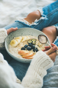 Woman in jeans and sweater eating healthy vegan breakfast  close up