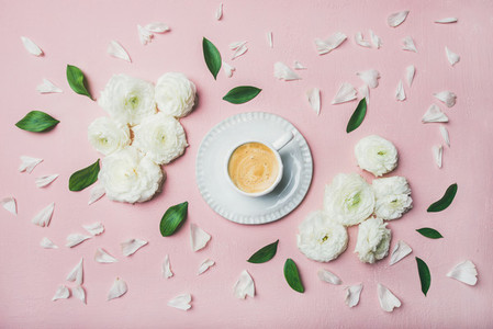 Cup of coffee surrounded with white ranunculus flowers and petals