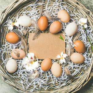 Natural colored eggs for Easter in basket over grey background
