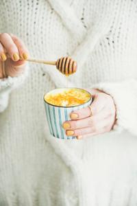 Turmeric latte golden milk with honey in womans hands