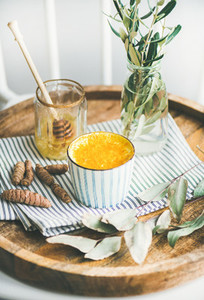 Turmeric latte or golden milk with honey in cup