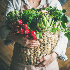 Female farmer holding basket with fresh vegetables square crop