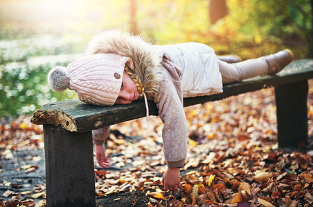 Little girl laying on bench in forest