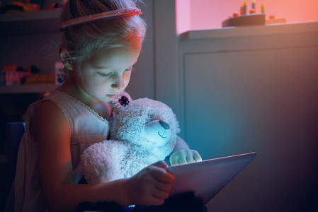 Little child browsing tablet with toy bear