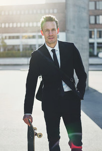 Confident man wearing suit standing with skateboard