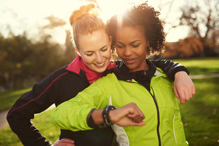 Two girlfriends in sportswear looking at watch