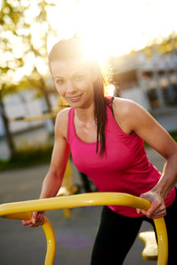 Woman smiling at camera standing on stationary bike