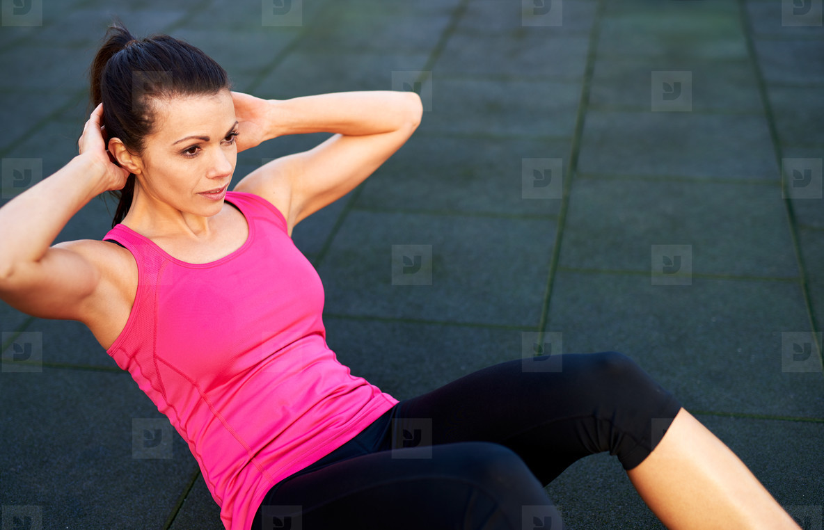Woman on floor doing situps outside