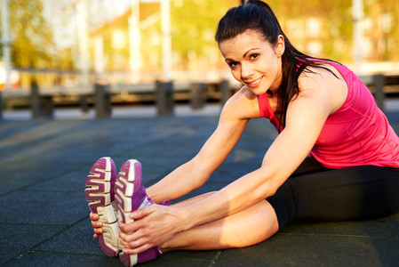 Woman stretching hamstrings and smiling