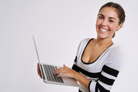 Happy smiling young woman using a laptop