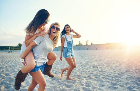 Three happy girlfriends running on the beach