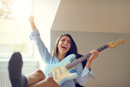 Singing woman playing guitar with feet on table