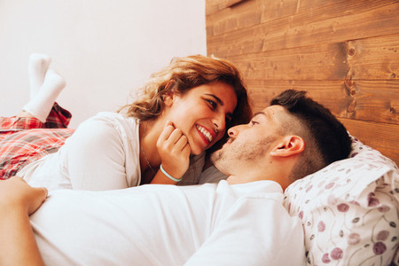Young smiling heterosexual couple lying down together on the bed