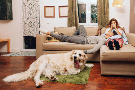 Young smiling couple together on sofa whit their dog