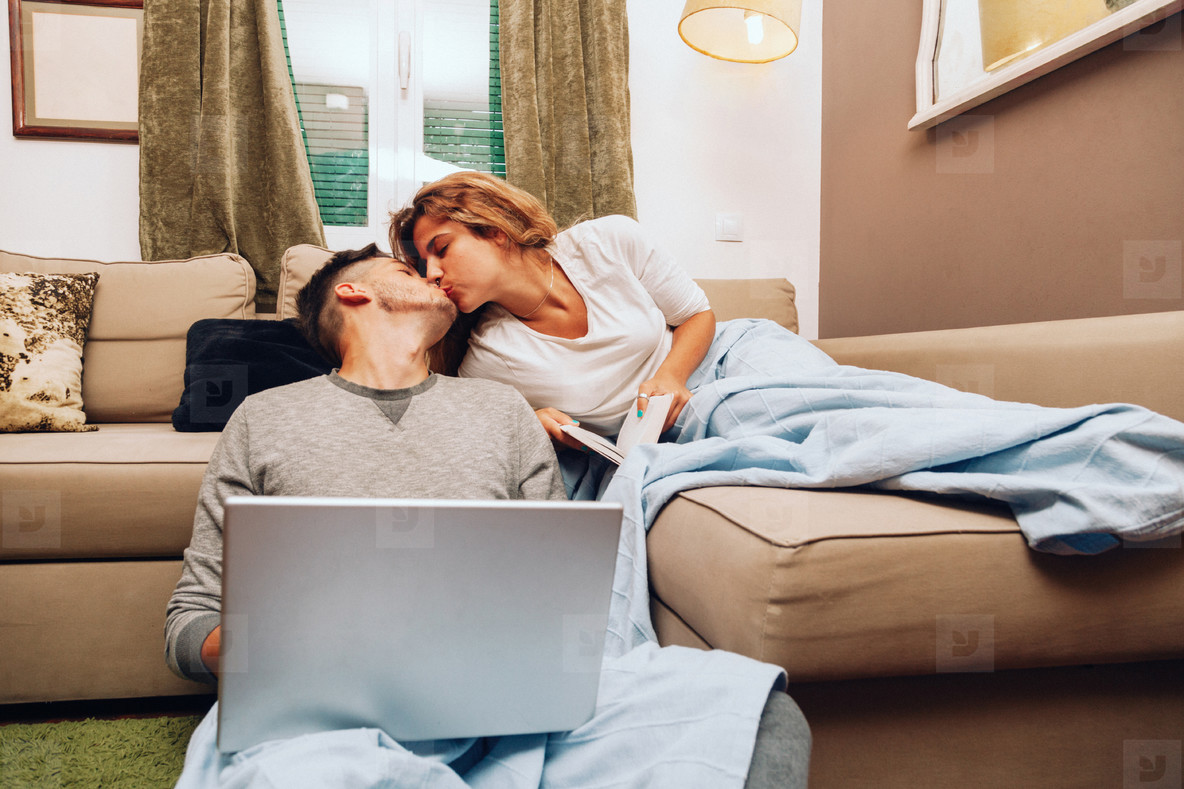 Young smiling heterosexual couple together on sofa