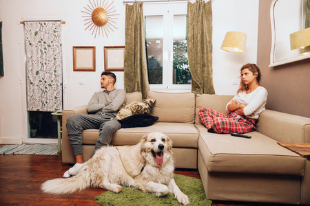 Young angry couple separated on sofa whit their dog