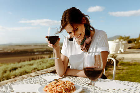 Woman sitting at a dining table drinking wine