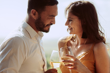Close up of a smiling couple together holding wine glasses