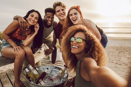 Woman talking selfie with friends at the beach party