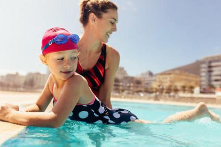 Mother teaching her daughter to swim