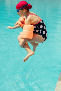 Girl jumping into the swimming pool