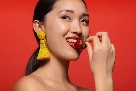 Pretty woman eating fresh strawberry