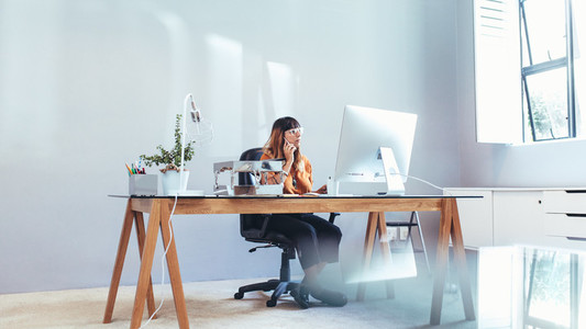 Businesswoman working on computer sitting in office