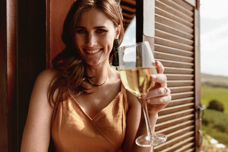 Portrait of a smiling woman drinking white wine