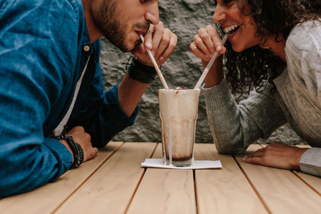 Loving couple sharing milkshake