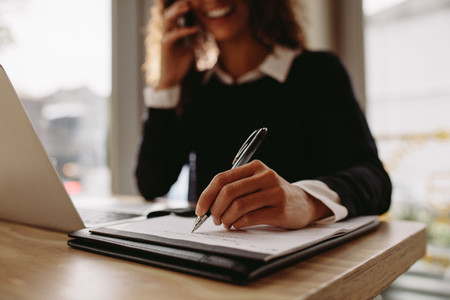 Woman making notes at cafe