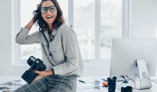 Smiling female photographer in office