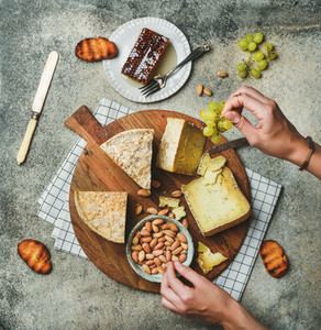 Cheese platter with female hands reaching to food