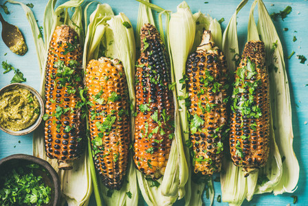 Flat lay of grilled sweet corn with spices