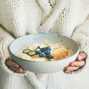 Woman in sweater holding bowl of oatmeal porriage square crop