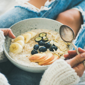 Woman in jeans and sweater eating oatmeal porriage  square crop