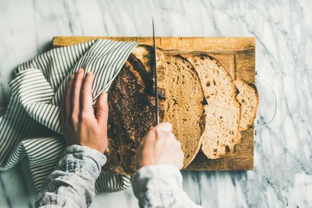Female hands cutting freshly baked sourdough bread