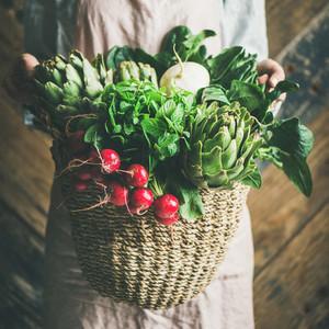 Female farmer holding basket of fresh garden vegetables square crop