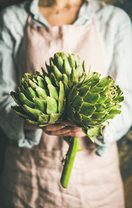 Female farmer holding fresh artichokes
