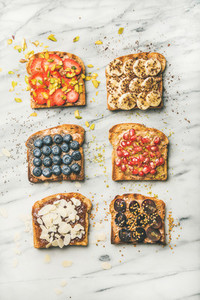 Vegan toasts with fruit  seeds  nuts and peanut butter