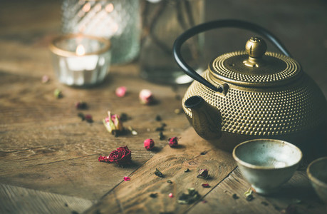 Golden iron teapot cups dried rose candles over wooden background