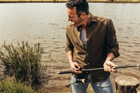 Portrait of a man standing near a lake holding a fishing rod