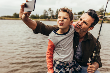 Man taking selfie with his kid outdoors