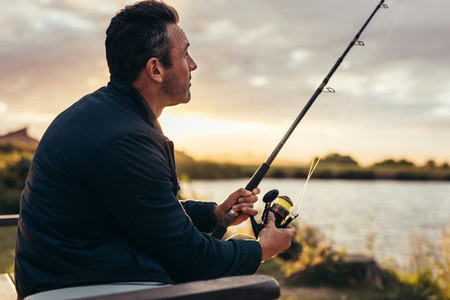 Man sitting near a lake with fishing rod
