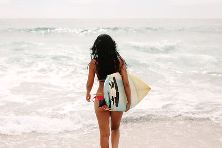 Surfer girl going in the water
