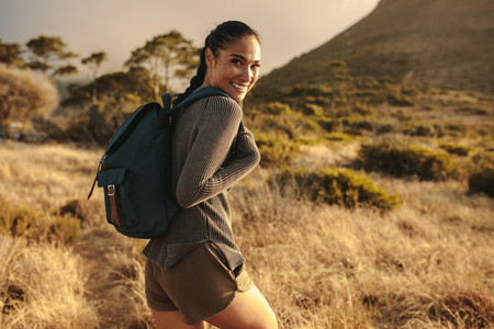 Woman with backpack walking up the country trail