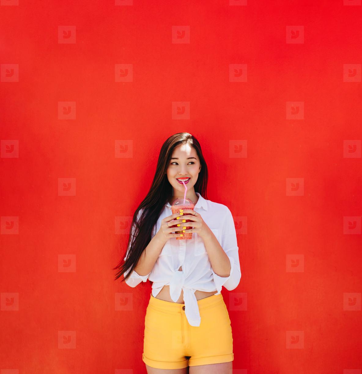 Smiling woman enjoying a smoothie