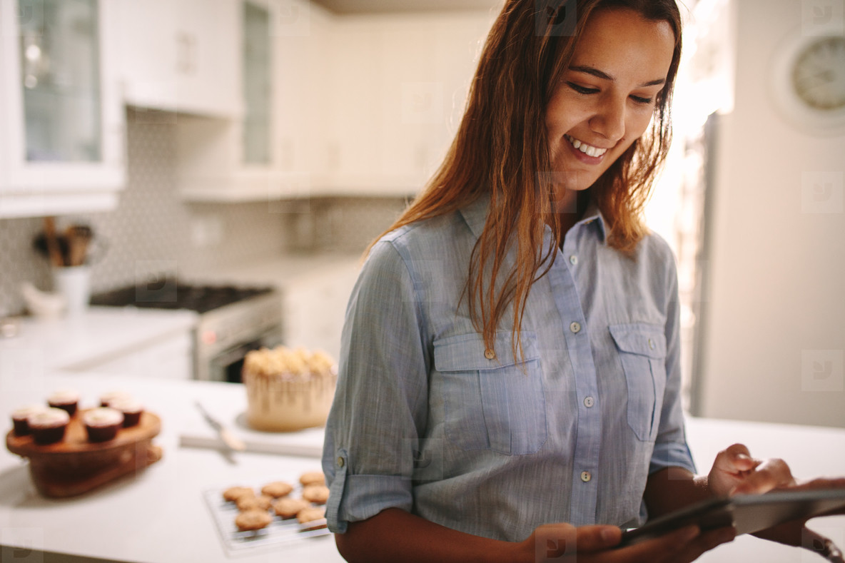 Pastry chef using digital tablet in kitchen
